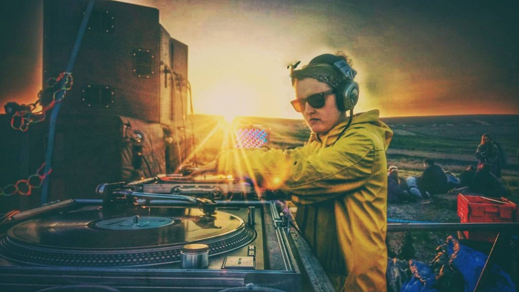 K Super behind the turntables of an outdoor event at sunrise.